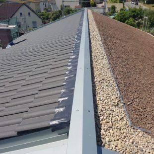Dach wo man auf einer Seite Dachkies sieht und auf der anderen Dachschindeln