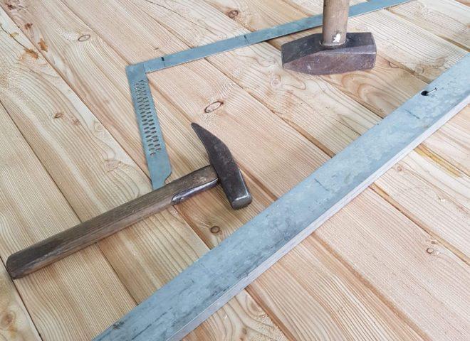 Hammer und andere Werkzeuge stehen und liegen auf Holz